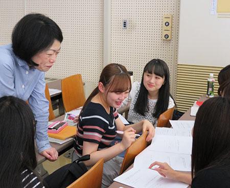学生のグループ討議を指導する石川由香里教授(左)。時には同じ女性目線での助言も