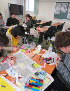 どの記事を選ぼうか。新聞を互いに読みながら気になるニュースを探す学生ら