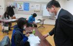 感染症予防のためマスク姿で原稿用紙に向かう小中学校の若手教諭。渥美清孝さん(右端)の指導は懇切丁寧だ